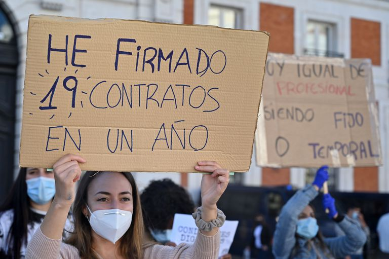 """A healthcare worker holds a sign reading """"I signed 19 contracts in one year"""" at a protest in Puerta del Sol in Madrid on Spain's National Day, October 12."""