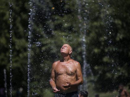 A man cools off in Madrid Rio park.