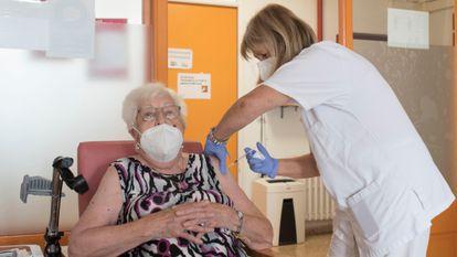 A nursing home resident receives a third shot of a Covid-19 vaccine.