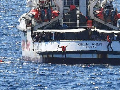 Migrants jump from the 'Open Arms' into the sea.