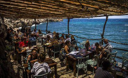 Diners at a beach bar in Cala Deià.