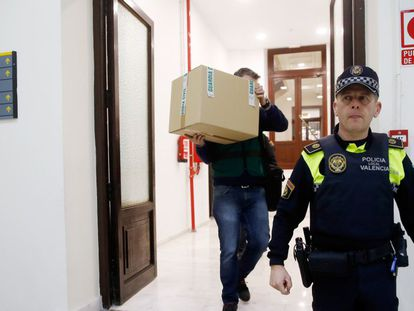 An investigator takes away a box from Popular Party offices in Valencia on Tuesday.