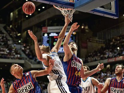 Real Madrid captain Felipe Reyes fights for a rebound with Barça's Sarunas Jasikevicius and Ante Tomic.