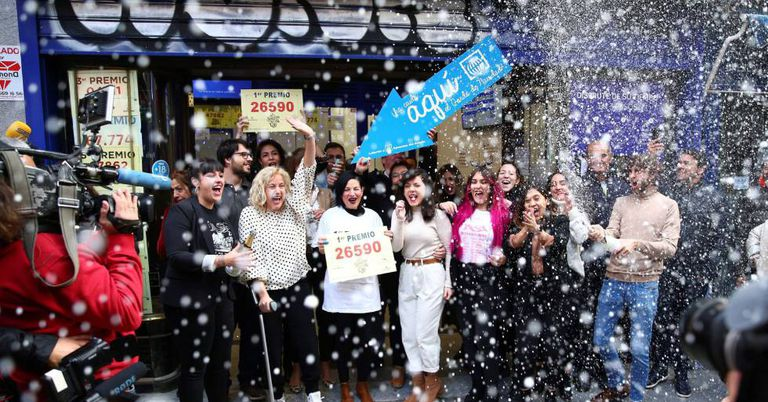 People celebrate at Madrid's famous Doña Manolita lottery shop, which sold the top prize.