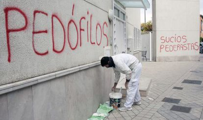 A painter covers up graffiti in the parish where suspect Father Román worked.