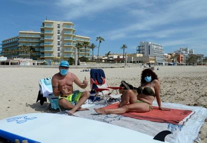 Beachgoers wearing face masks on a beach in Mallorca in Spain's Balearic Islands.