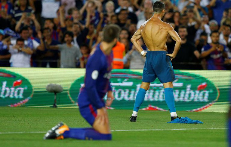Who's the daddy? Piqué looks on at a shirtless Cristiano Ronaldo.