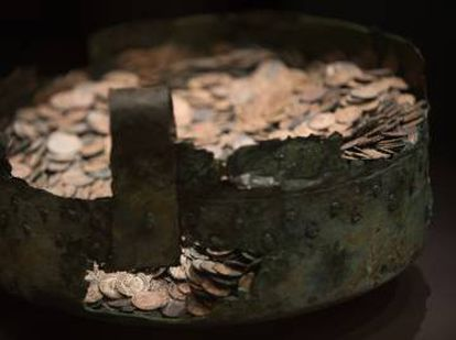 The restored cauldron and Roman coins.