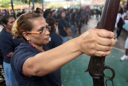A woman holds a shotgun during the presentation of armed vigilante group - Citizens Self-Protection Police - in Acapulco, Guerrero state.