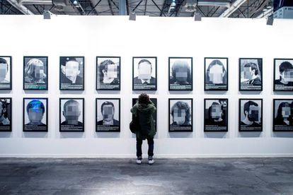 A woman in front of the Santiago Sierra installation that was taken down.