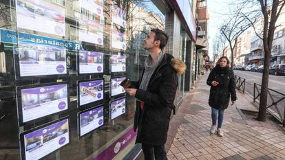 A young man reads property listings in Madrid.