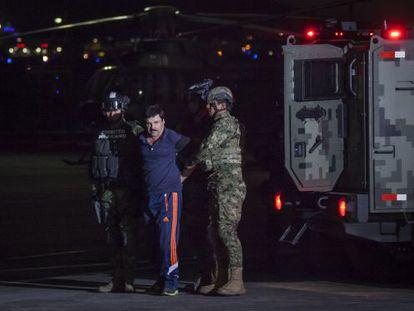 """Two soldiers escort """"El Chapo"""" Guzmán."""