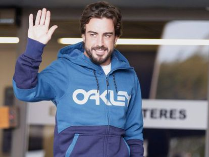 Alonso waves to the press as he leaves hospital.