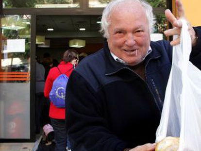 A pensioner displays a loaf purchased from Pepe Navarro´s bakery