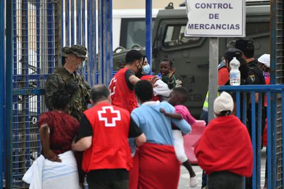 Red Cross members help several women and children as they arrive in Ceuta on Wednesday.