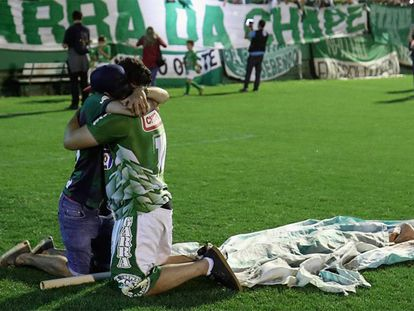 Two fans hug during a tribute to Chapecoense