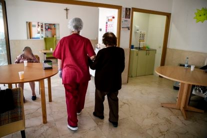 A worker helps a resident at the Santa María de Montecarmelo senior home in Madrid.