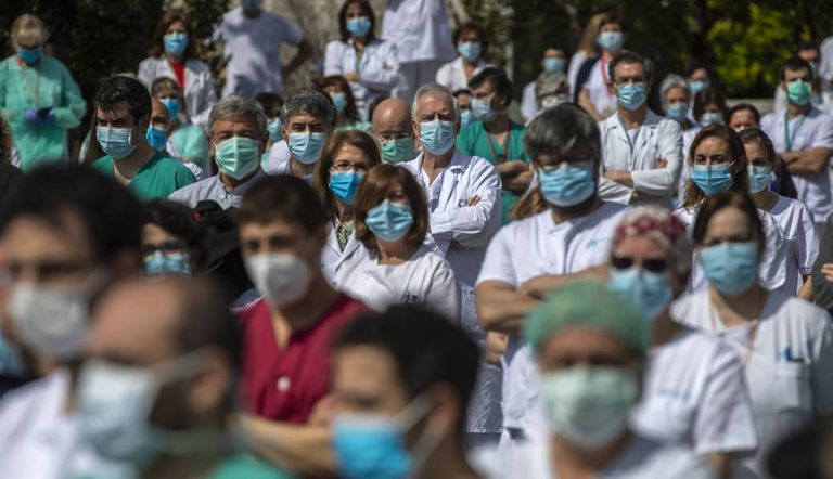 Health workers at the La Paz hospital in Madrid hold a minute of silence in tribute to a doctor who died from Covid-19.