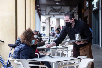 A waiter serves a patron in a café in Badajoz.