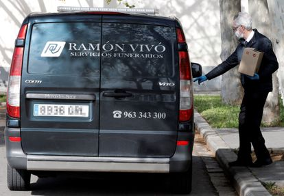 A worker from a funeral service collects the ashes of a coronavirus victim in Valencia.