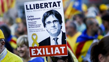 A pro-independence demonstrator holds up a Puigdemont sign.