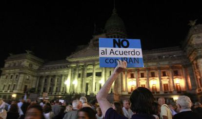 A man holds up a sign during a demonstration to protest against the agreement between Argentina and Iran.