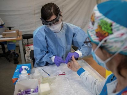 A health worker performs a fast coronavirus test on an emergency worker in Madrid.