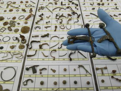 """A civil guard holds up some of the archaeological items recovered during so-called """"Operation Helmet."""""""