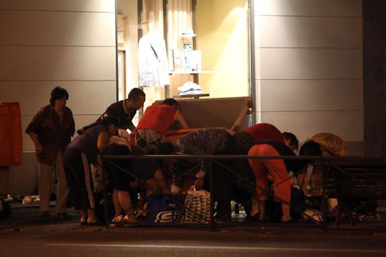 A photo taken in June 2012 shows a group of people rummaging through dumpsters placed at the exit of a shopping mall in Madrid.