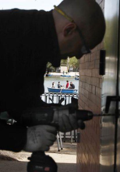 A municipal workman breaks the lock to the door of a quiosco before padlocking it shut.