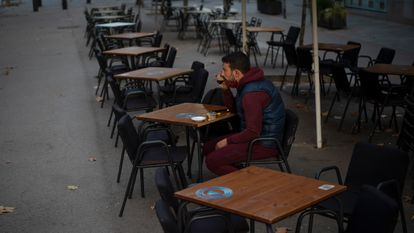 A customer sits at an empty sidewalk café in Barcelona, where new restrictions on the food service industry will come into effect on Monday.