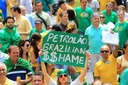 """A woman holds up a sign reading """"Brazilian Oil $$hame"""" during Sunday's protests held against Rousseff's policies."""