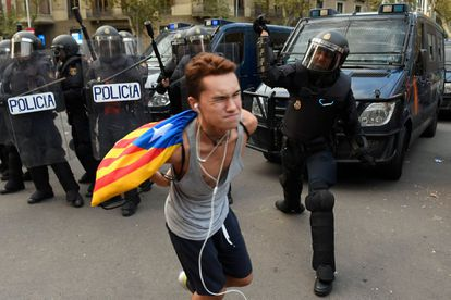 An officer hits a protester during this Saturday's protest in Barcelona.