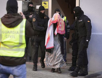 The authorities escort one of the detainees in this morning's raid.