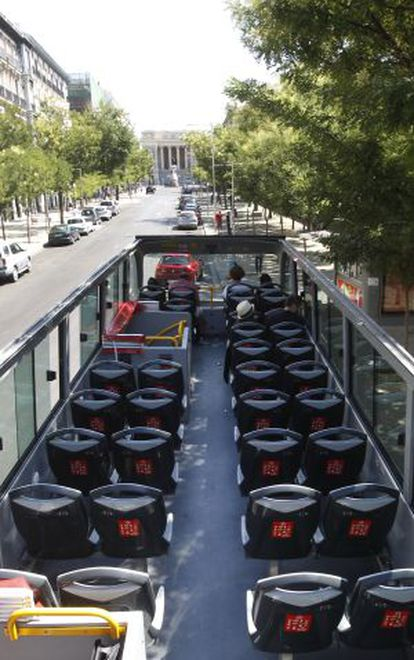 A near-empty tourist bus cruises the streets of Madrid during the summer.
