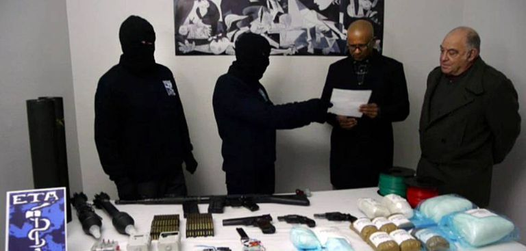Hooded ETA members hand over an inventory of weapons to a verification group in February 2014.