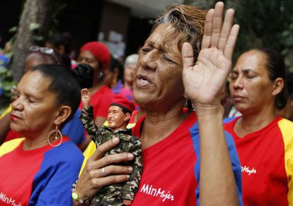 A woman holds a figurine of Chávez as she prays for his health in Caracas on Tuesday