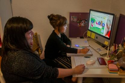 Mar Cadiñanos helping her daughter Vera, seven, with her homework at home in Madrid.