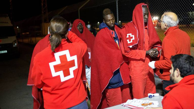 Red Cross staff tend to immigrants rescued from a dinghy in Motril.