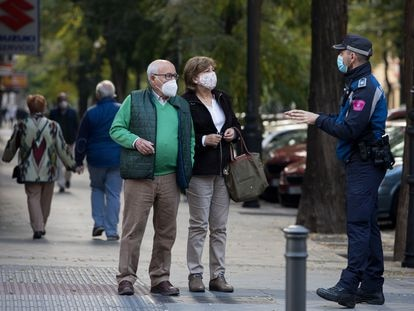 A local police officer informs a couple about the coronavirus restrictions in Madrid.
