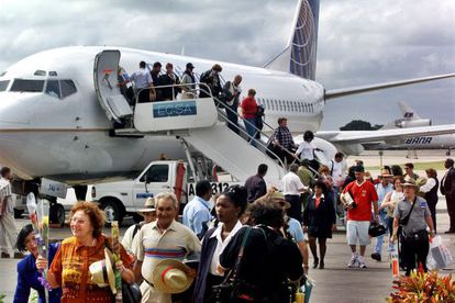 Passengers on a chartered flight from Florida arrive in Havana.