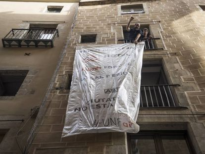 Activists unfurl a banner protesting against illegally let apartments.