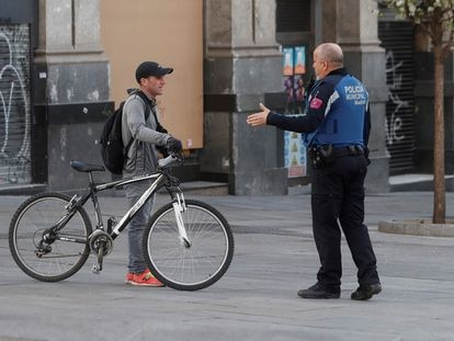 A Madrid local police officer tells a member of public that he cannot ride his bicycle under the state of alarm decreed in Spain on Saturday.