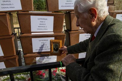 Rafael Martínez Martínez, with a photo of his father by his father's remains.