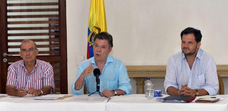 Santos (center) speaks to reporters in Cartagena de Indias alongside chief negotiator Humberto De la Calle (left) and Peace Commissioner Sergio Jaramillo.