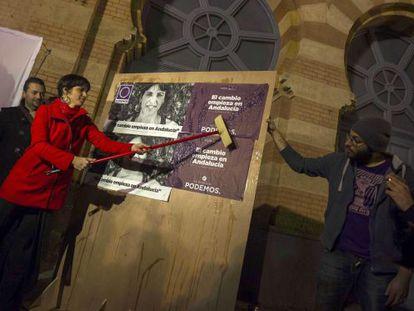 Podemos candidate Teresa Rodríguez puts up a campaign poster.