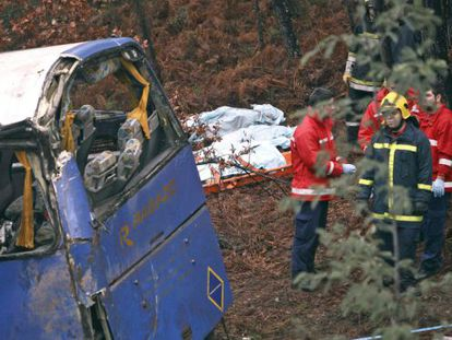 Firefighters stand next to bodies covered by blankets and the bus that fell into a ravine in Sertã district of Castelo Branco on Sunday.