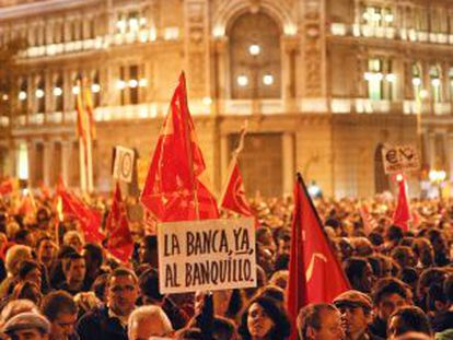 Protesters in Madrid carry placards asking why their money is being used to bail out banks.