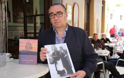 Joaquín García de Romeu holds a photo of Cándida next to his book, 'The Last Black Woman.'