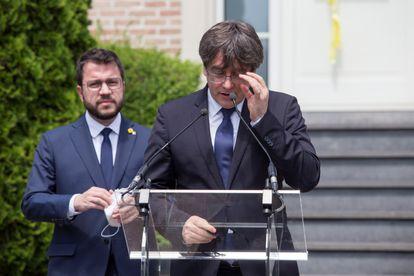 Ex-Catalan premier Carles Puigdemont speaking in Waterloo (Belgium) while current Catalan leader Pere Aragonès looks on.